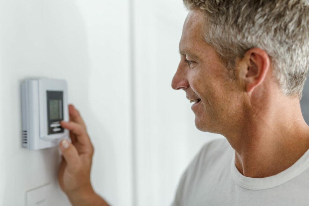 Man adjusts his home thermostat Alberta Heating Company