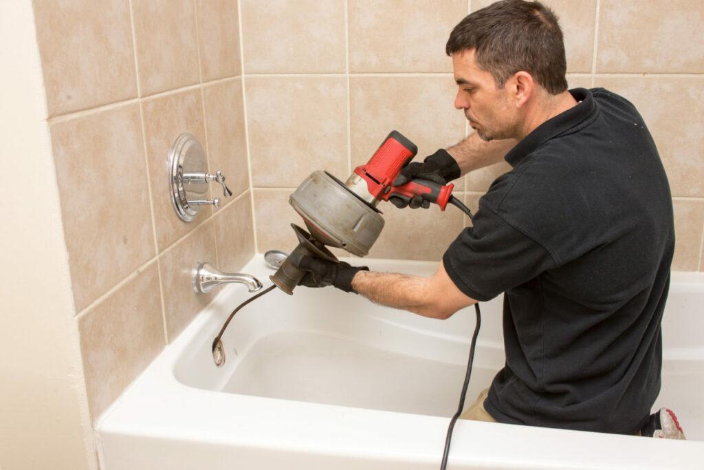 Edmonton Plumber snaking a clogged drain in a bathtub